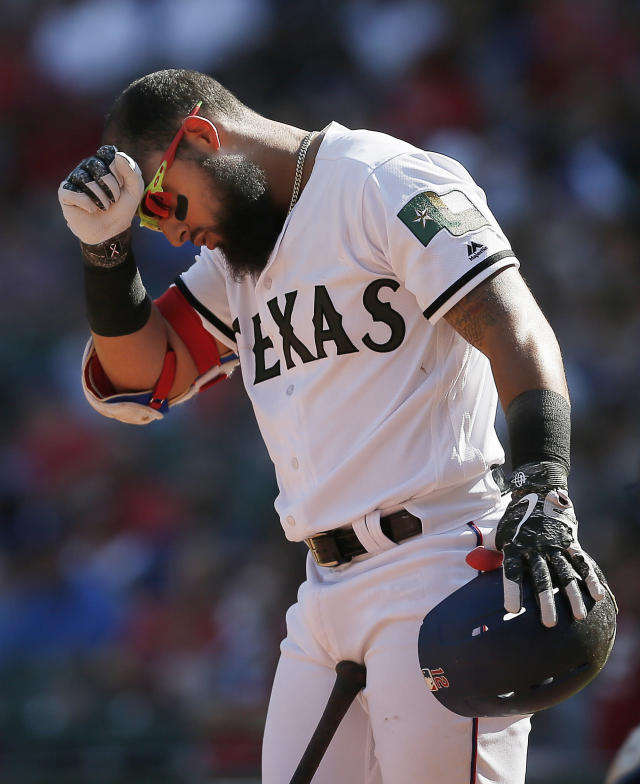Texas Rangers' Rougned Odor (12) wipes sweat from his forehead during the fourth inning of a baseball game against the Kansas City Royals, Saturday, May 26, 2018, in Arlington, Texas. Texas won 4-3 in 10 innings. (AP Photo/Brandon Wade)