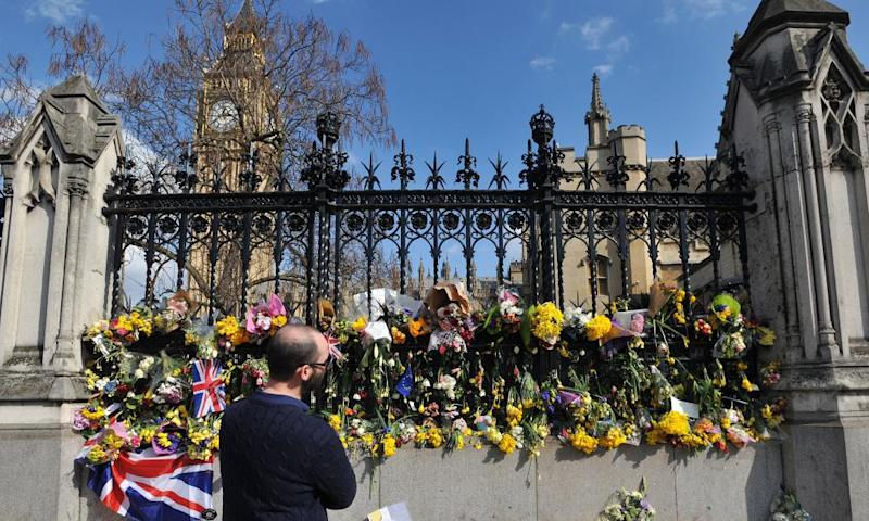 A man looks at floral tributes to the victims of the Westminster terrorist attack.