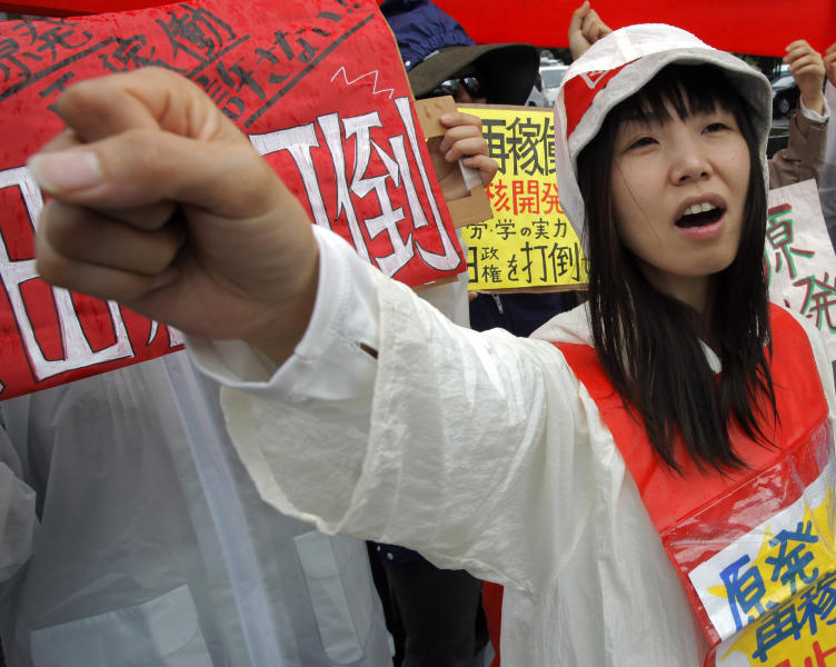 """A demonstrator raises clenched fist during a rally, protesting against restarting the Ohi nuclear power plant's reactors in front of the prime minister's official residence in Tokyo, Saturday, June 16, 2012. Japan moved closer to restarting the nuclear reactors for the first time since last year's earthquake and tsunami led to a nationwide shutdown. A slogan worn by the protester reads: """"Stop restarting nuclear power plant."""" (AP Photo/Itsuo Inouye)"""