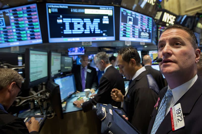Traders gather at the post that trades IBM on the floor of the New York Stock Exchange