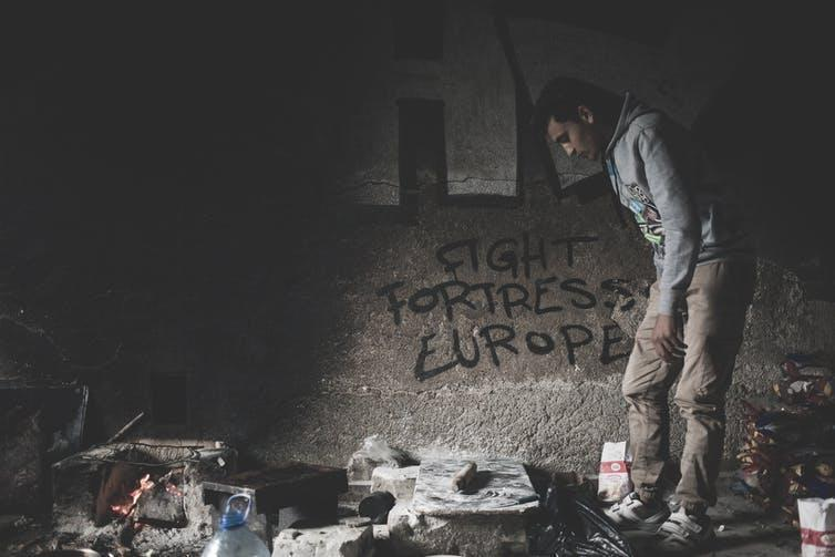 A man looks around a dark room in a migrant camp. Graffiti on the wall reads 'Fight Fortress Europe'.