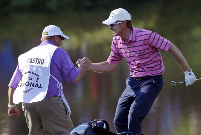 Roberto Castro, right, celebrates with his caddie Rusty Stark after making a chip to save par on the 18th green during the third round of the AT&T National golf tournament at Congressional Country Club, Saturday, June 29, 2013, in Bethesda, Md.(AP Photo/Patrick Semansky)