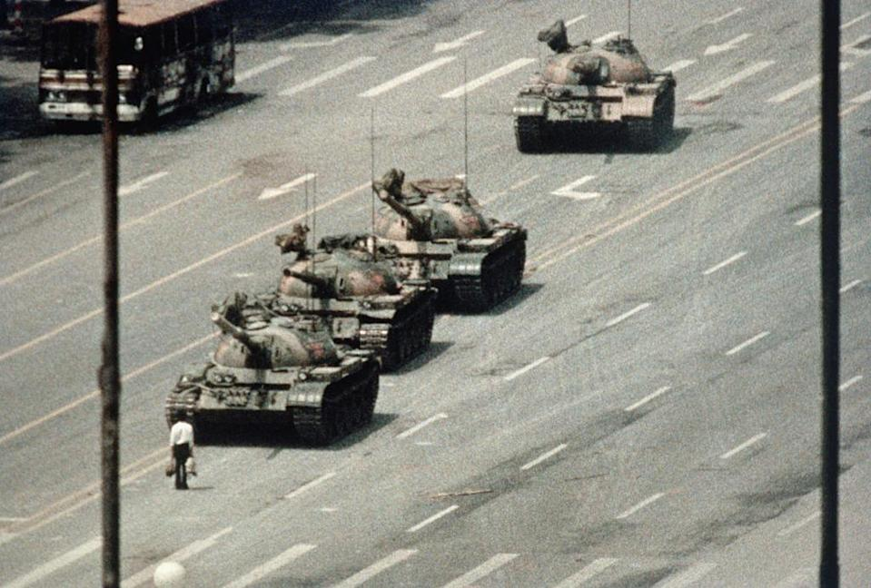 Tank man staring down a line of tanks as he block their path