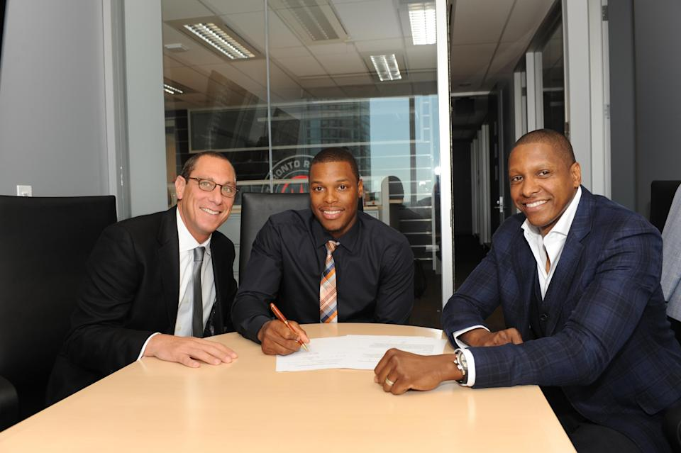 Agent Andy Miller (L) poses with client Kyle Lowry (C) and Toronto Raptors GM Masai Ujiri during the signing of a contract extension on July 10, 2014. (Getty)