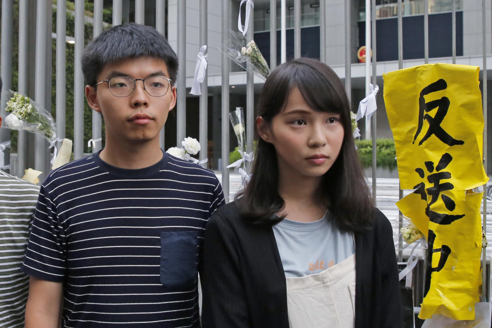 In this June 18, 2019, photo, pro-democracy activists Agnes Chow, right, and Joshua Wong meet media outside government office in Hong Kong. Demosisto, a pro-democracy group in Hong Kong posted on its social media accounts that well-known activist Joshua Wong had been pushed into a private car around 7:30 a.m. Friday, Aug. 30, 2019 and was taken to police headquarters. It later said another member, Agnes Chow, had been arrested as well. (AP Photo/Kin Cheung)