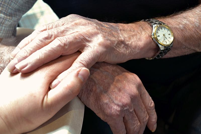 Two elderly hands holding onto one hand of a younger adult.