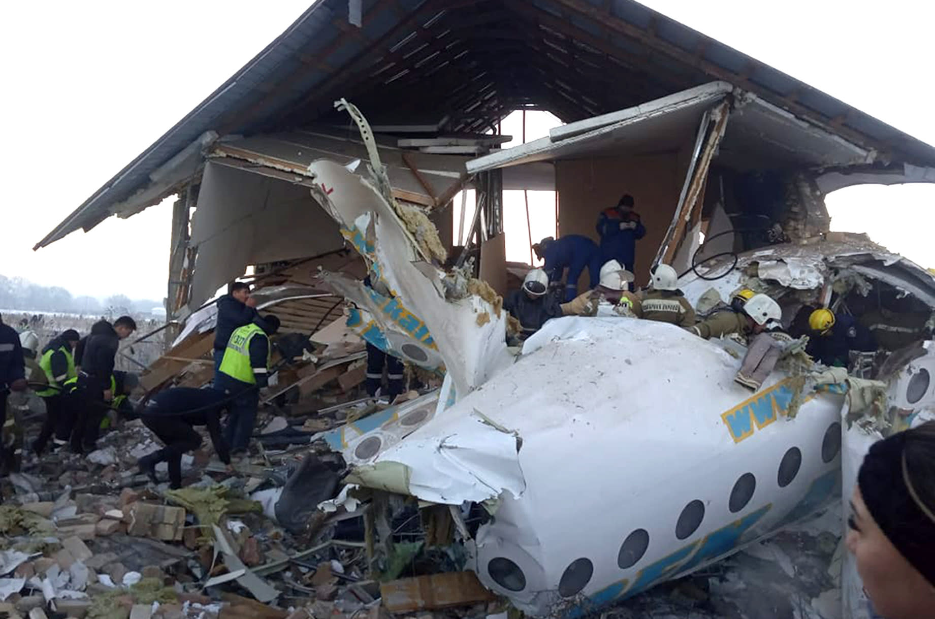 In this handout photo provided by the Emergency Situations Ministry of the Republic of Kazakhstan, police and rescuers work on the side of a plane crash near Almaty International Airport, outside Almaty, Kazakhstan, Friday, Dec. 27, 2019. Almaty International Airport said a Bek Air plane crashed Friday in Kazakhstan shortly after takeoff causing numerous deaths. The aircraft had 100 passengers and crew onboard when hit a concrete fence and a two-story building shortly after takeoff. ( Emergency Situations Ministry of the Republic of Kazakhstan photo via AP)