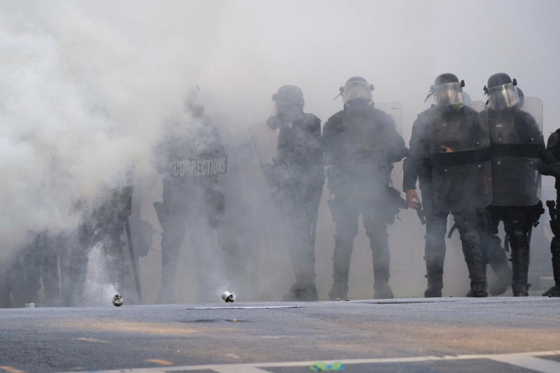 Police stand near tear gas during a demonstration Monday, June 1, 2020, in Atlanta over the death of George Floyd, who died May 25 in Minneapolis. (Ben Gray/Atlanta Journal-Constitution via AP)