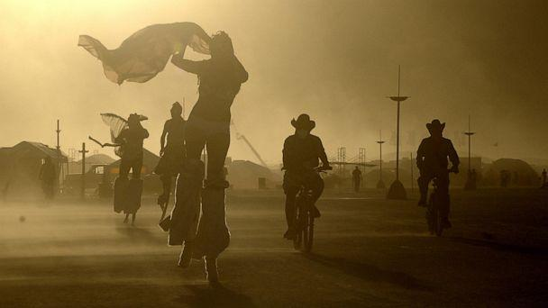 PHOTO: A windstorm whips sand at Burning Man as participants take evening bike rides and strolls on stilts in Black Rock Desert, Nev., Aug. 8, 2005. (Jim Rankin/Toronto Star via Getty Images)