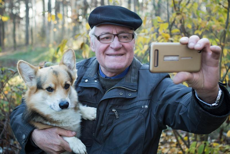 Older man outdoors holding dog and taking selfie