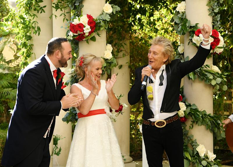 LAS VEGAS, NEVADA - OCTOBER 02: (EXCLUSIVE COVERAGE) Sir Rod Stewart (R) sings during the wedding of Sharon Cook (C) and Andrew Aitchison (L) from Liverpool, England. The wedding was nearly cancelled due to the Thomas Cook Bankruptcy. Caesars Palace and Delta Air Lines flew the couple and their guests to Las Vegas as originally planned. The Wedding took place at Caesars Palace on October 02, 2019 in Las Vegas, Nevada. (Photo by Denise Truscello/WireImage)