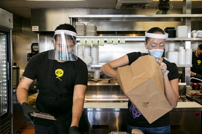 Shift leader Jonathan Garcia and general manager Brenda Oropeza prepare takeout orders as diners eat at Saffron Thai on May 21, 2020 in San Diego, California. Restaurants began reopening for dine-in patrons on Thursday as the state and county began easing restrictions imposed during the coronavirus pandemic.
