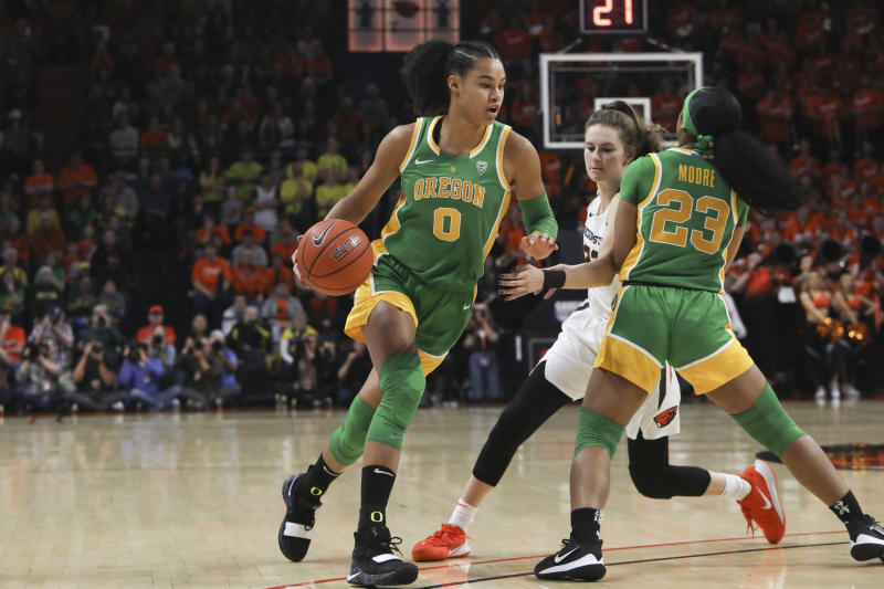 Oregon's Satou Sabally (0) drives to the basket around teammate Minyon Moore (23) and Oregon State's Kat Tudor (22) during the first half of an NCAA college basketball game in Corvallis, Ore., Sunday, Jan. 26, 2020. (AP Photo/Amanda Loman)