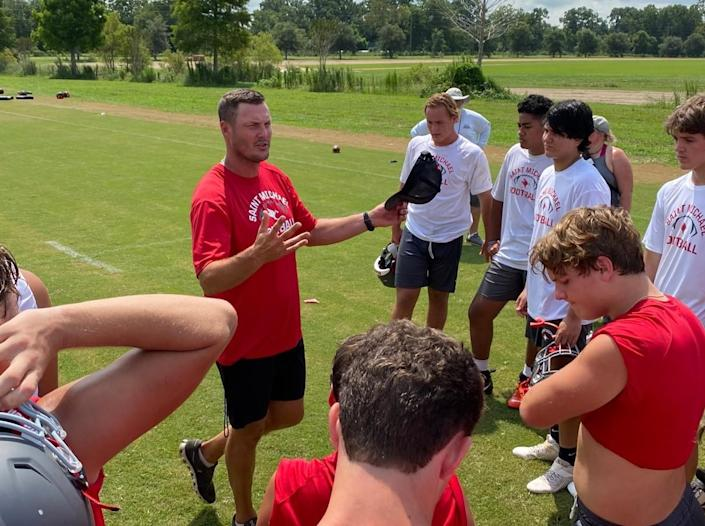 Retired NFL quarterback Philip Rivers talks to his players at St. Michael Catholic High in Fairhope, Ala.
