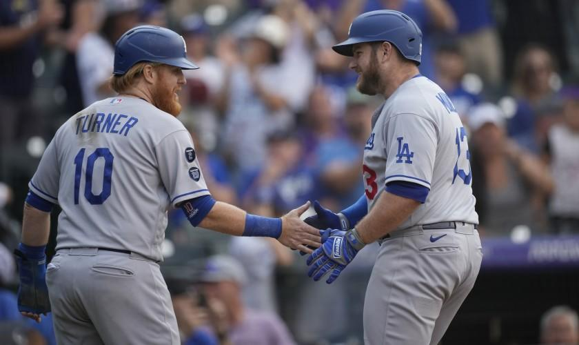 Los Angeles Dodgers' Justin Turner, left, congratulates Max Muncy who crossed home plate following his two-run home run off Colorado Rockies relief pitcher Lucas Gilbreath in the 10th inning of a baseball game Thursday, Sept. 23, 2021, in Denver. (AP Photo/David Zalubowski)