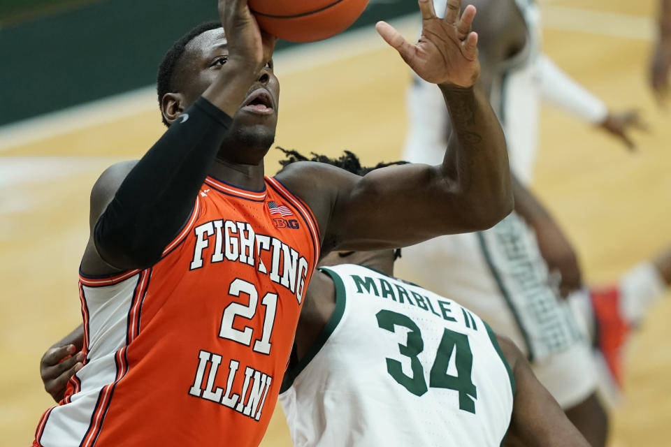 Illinois center Kofi Cockburn (21) makes a layup as Michigan State forward Julius Marble II (34) defends during the first half of an NCAA college basketball game, Tuesday, Feb. 23, 2021, in East Lansing, Mich. (AP Photo/Carlos Osorio)