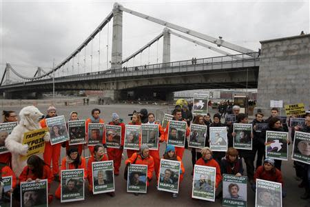 Greenpeace activists hold portraits of those detained on the boat Arctic Sunrise during a protest in Moscow