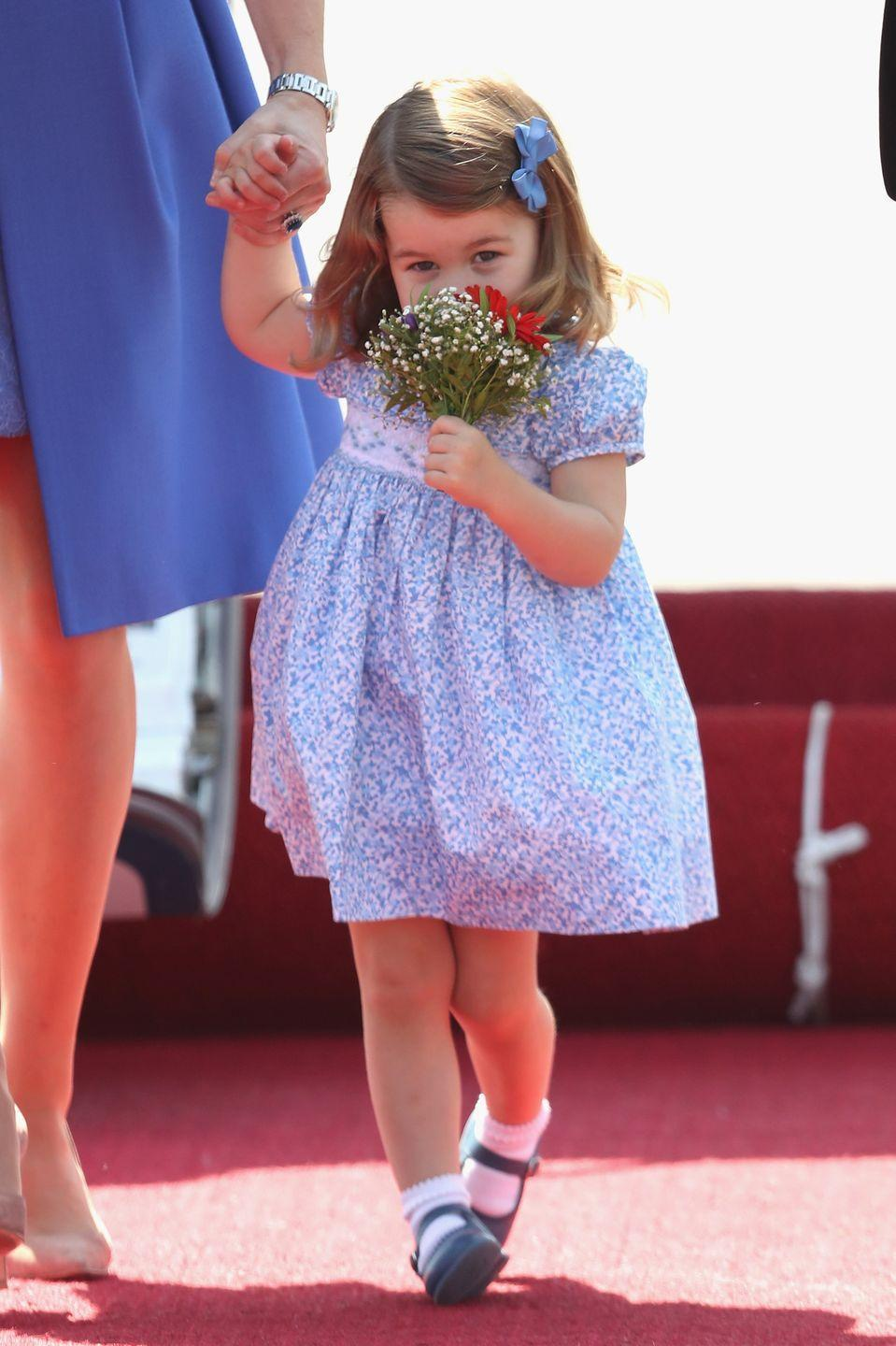 <p>Princess Charlotte smells a fresh bouquet of flowers that she was given as she arrived in Berlin, Germany for her second royal tour in 2017. </p>