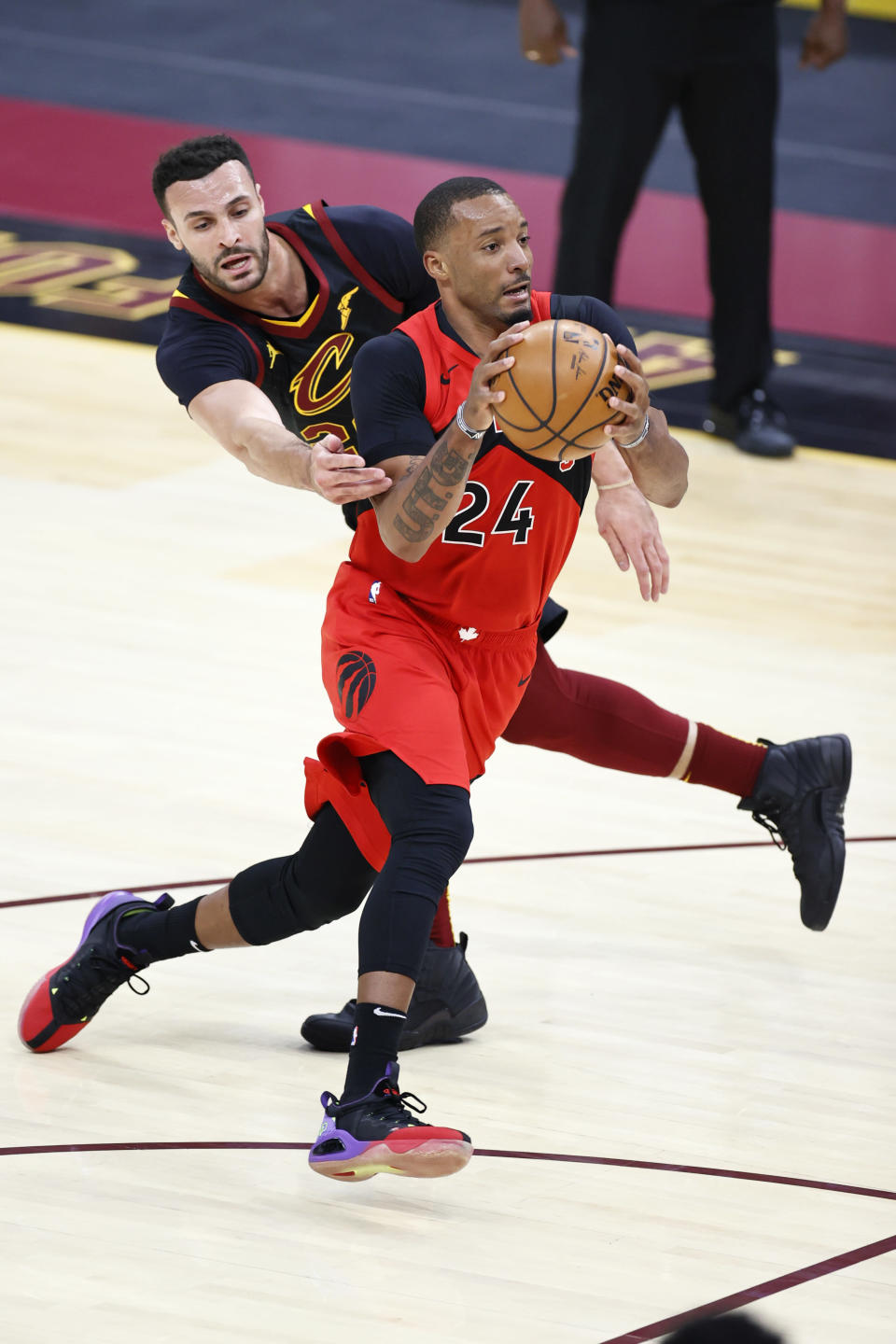 Toronto Raptors' Norman Powell (24) drives past Cleveland Cavaliers' Larry Nance Jr. (22) in the second half of an NBA basketball game, Sunday, March 21, 2021, in Cleveland. (AP Photo/Ron Schwane)