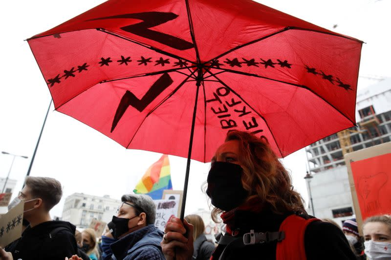 A woman holds an umbrella as she takes part in a protest against the ruling by Poland's Constitutional Tribunal that imposes a near-total ban on abortion in Warsaw
