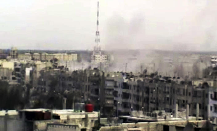 In this image made from amateur video released by the Shaam News Network and accessed Sunday, April 15, 2012, smoke rises from buildings across the city following purported shelling in Homs, Syria. Syrian troops are reported to have shelled residential neighborhoods dominated by rebels in the central city of Homs Sunday, activists said, killing at least three people hours before the first batch of United Nations observers were to arrive in Damascus to shore up a shaky truce. (AP Photo/Shaam News Network via AP video) TV OUT, THE ASSOCIATED PRESS CANNOT INDEPENDENTLY VERIFY THE CONTENT, DATE, LOCATION OR AUTHENTICITY OF THIS MATERIAL