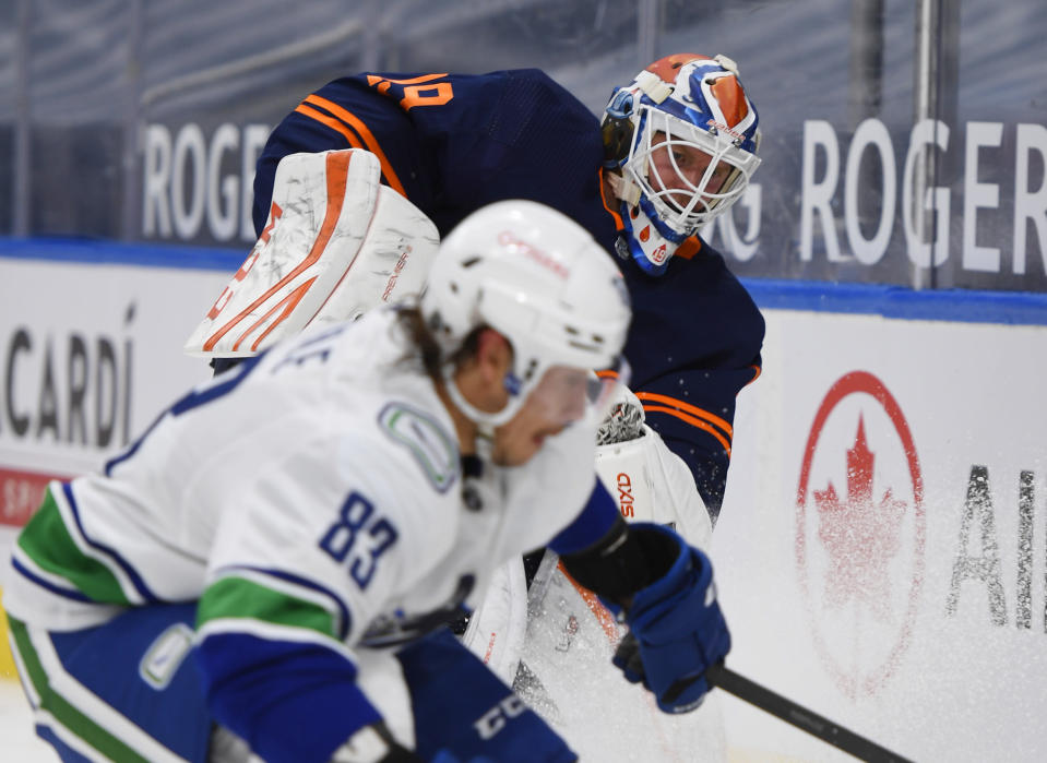 Edmonton Oilers goalie Mikko Koskinen (19) and Vancouver Canucks' Jay Beagle (83) work for the puck during the third period of an NHL hockey game Wednesday, Jan. 13, 2021, in Edmonton, Alberta. (Dale MacMillan/The Canadian Press via AP)