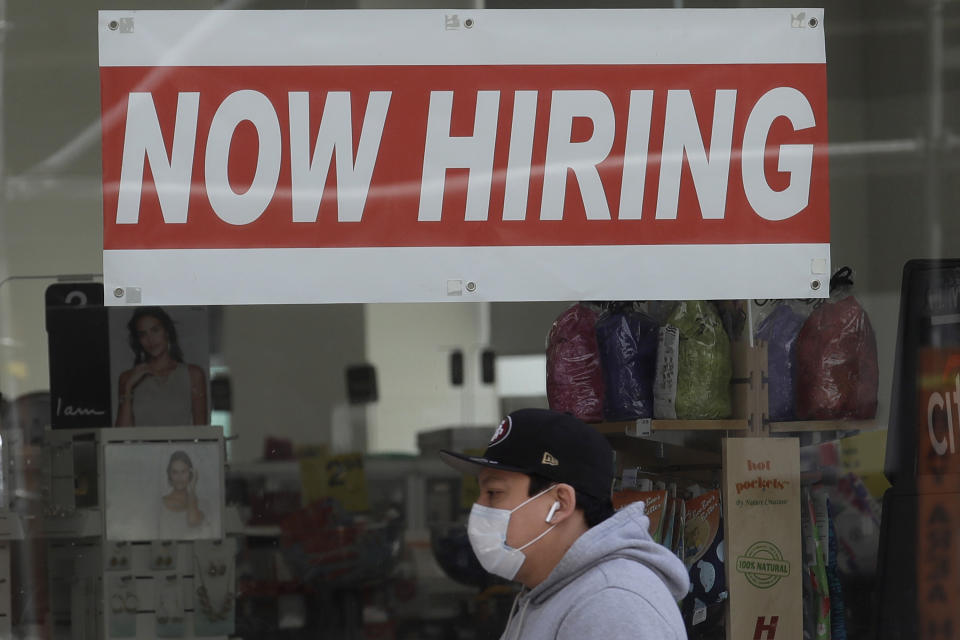 FILE - This May 7, 2020, file photo shows a man wearing a mask while walking under a Now Hiring sign at a CVS Pharmacy during the coronavirus outbreak in San Francisco.  On Thursday, Nov. 12, the number of people seeking unemployment benefits fell last week to 709,000, the fourth straight drop and a sign that the job market is slowly healing. The figures coincide with a sharp resurgence in confirmed viral infections to an all-time high above 120,000 a day.  (AP Photo/Jeff Chiu, File)