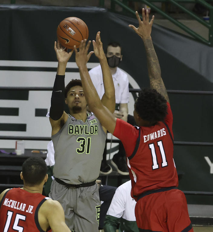 Baylor guard MaCio Teague (31) shoots a 3-point shot past Texas Tech guard Kyler Edwards (11) in the second half of an NCAA college basketball game Sunday, March 7, 2021, in Waco, Texas. (AP Photo/Jerry Larson)