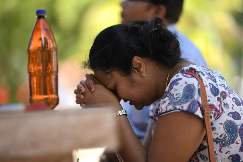 A woman prays at St. Sebastian's Church in Negombo a day after the blasts (AFP/Getty Images)