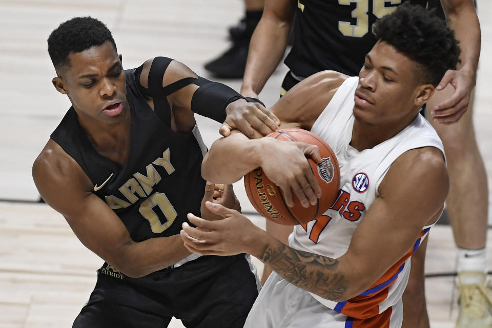 Army's Josh Caldwell, left, and Florida's Keyontae Johnson fight for possession of the ball in the second half of an NCAA college basketball game, Wednesday, Dec. 2, 2020, in Uncasville, Conn. (AP Photo/Jessica Hill)
