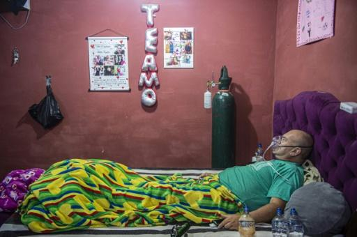 Venezuelan Wilmer Hernandez, 44, breathes from an oxygen mask at his home in a poor neighborhood of Lima, where most of his relatives have COVID-19