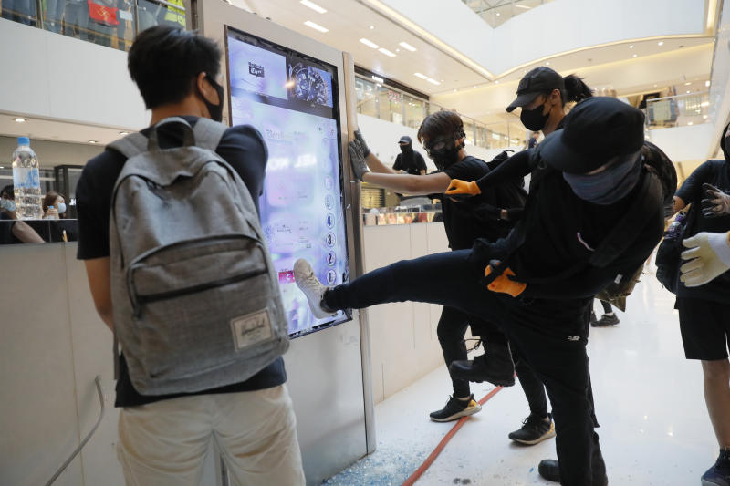 Protesters damage an electronic display board in a mall in Hong Kong on Sunday, Sept. 22, 2019. Protesters smashed surveillance cameras and electronic ticket sensors in a subway station, as pro-democracy demonstrations took a violent turn once again. (AP Photo/Kin Cheung)