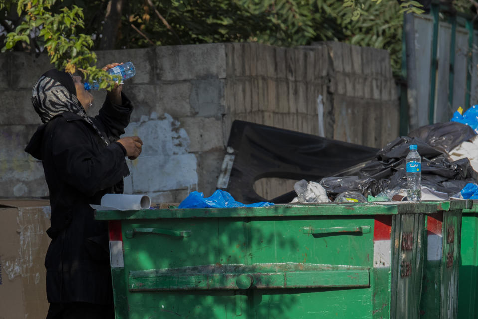 A homeless woman drinks water from a garbage dumpster in Beirut, Lebanon, Thursday, July 23, 2020. Lebanon should quickly form a reform-minded government to carry out badly needed reforms to help get the tiny country out of its severe economic crisis where the Real GDP growth is projected to contract nearly 20% in 2020 and a crash in local currency led to triple-digit inflation rates, the World Bank said Tuesday. (AP Photo/Hassan Ammar)