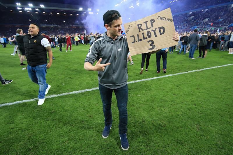 BIRMINGHAM, ENGLAND - MAY 15: Villa fans invade the pitch to celebrate victory as one of them holds a sign in tribute to the late Jlloyd Samuel at the end of the Sky Bet Championship Play Off Semi Final Second Leg match between Aston Villa and Middlesbrough at Villa Park on May 15, 2018 in Birmingham, England. (Photo by Simon Stacpoole/Offside/Getty Images)