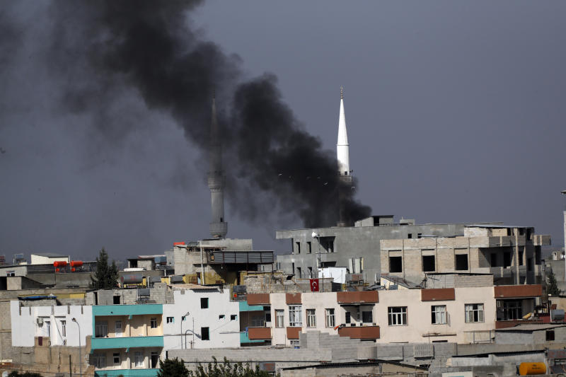 Smoke from a fire caused by an incoming mortar fired from the Syrian side, billows behind a mosque's minarets in Akcakale, Sanliurfa province, southeastern Turkey, smoke billows from targets inside Syria during bombardment by Turkish forces, Oct. 10, 2019. (Photo: Lefteris Pitarakis/AP)