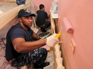 Soldiers painting a wall pink