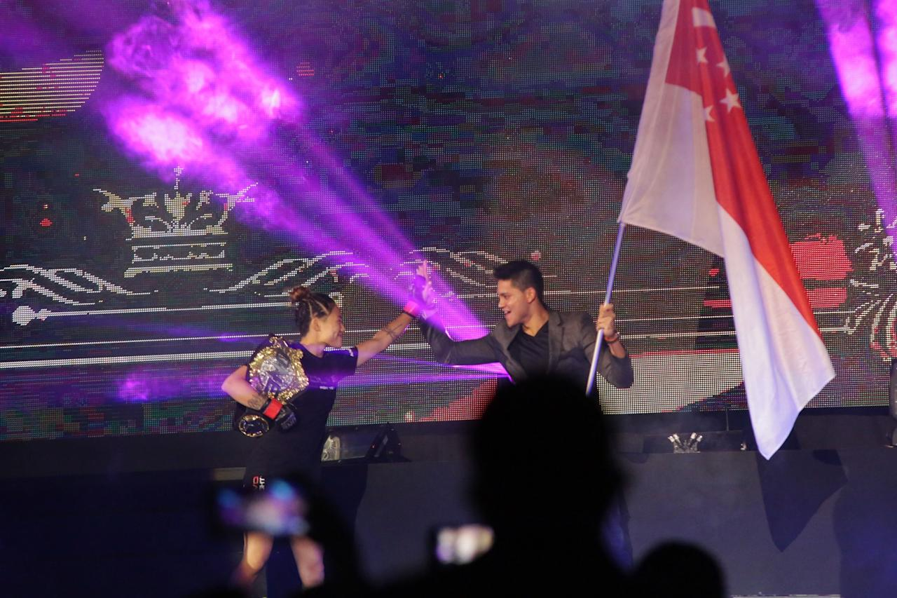 <p>Angela Lee gets a high-five from Singaporean Olympic champion Joseph Schooling during her entrance. (PHOTO: Dhany Osman / Yahoo Newsroom) </p>