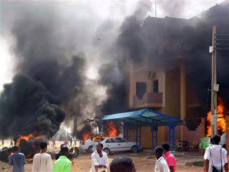 Cars burn in front of a building during protests over fuel subsidy cuts in Khartoum