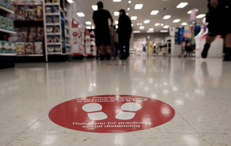 To protect from the coronavirus a social distancing spot is painted on the floor while shoppers wait in line at a Target store in the Van Nuys section of Los Angeles on Friday, April 24, 2020. (AP Photo/Richard Vogel)