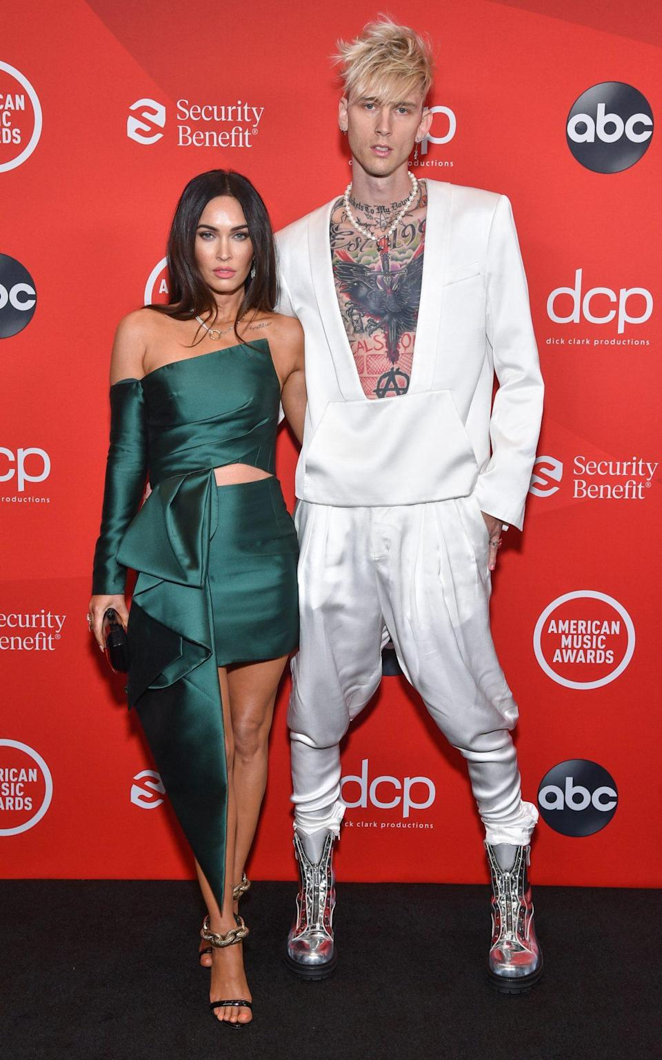 <p>Megan Fox's asymmetrical, emerald-green, one-sleeved mini almost got outshined by her beau Machine Gun Kelly's hybrid hoodie-tuxedo and futuristic metallic high-tops. Almost. </p>