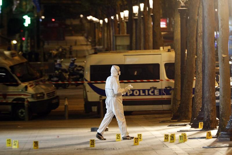Forensic experts investigate the crime scene after the shooting (AP)