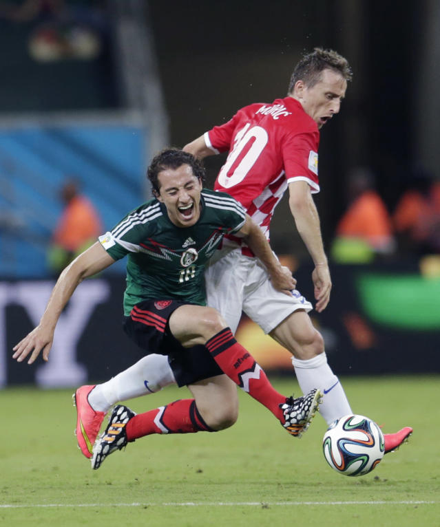Mexico's Andres Guardado, left, is challenged by Croatia's Luka Modric during the group A World Cup soccer match between Croatia and Mexico at the Arena Pernambuco in Recife, Brazil, Monday, June 23, 2014. (AP Photo/Petr David Josek)