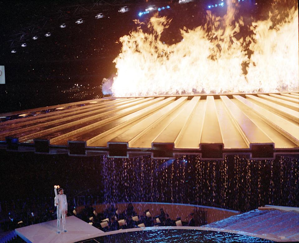 Torch Bearer Cathy Freeman made a dramatic entrance for the Sydney 2000 Olympic Games Opening Ceremony. The sprinter lit a ring of fire in a pool and waited for a saucer-like contraption to rise above her. But it didn't. For four agonizing minutes, she smiled and waited. A computer glitch was finally fixed and the flame flew up to meet the cauldron. (Ben Elters\Getty Images)