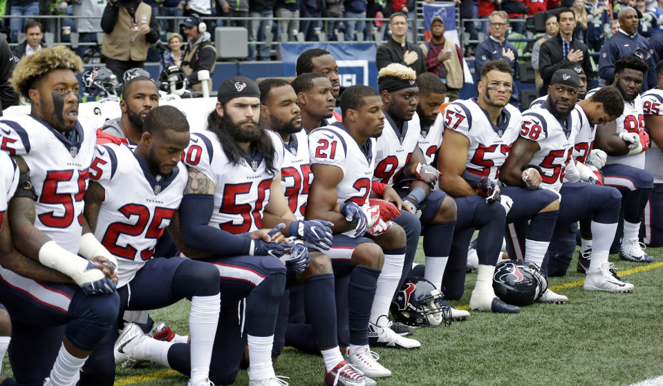 Texans players kneel during the singing of the national anthem before an October game in Seattle against the Seahawks. (AP)