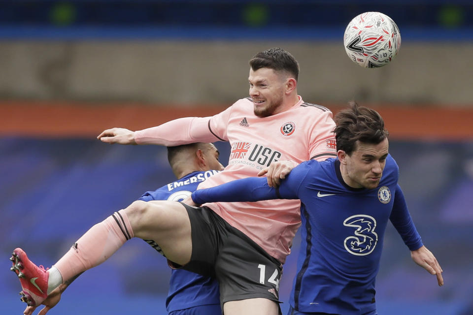 Sheffield United's Oliver Burke, left, jumps for a header with Chelsea's Ben Chilwell during the English FA Cup quarterfinal soccer match between Chelsea and Sheffield United at the Stamford Bridge stadium in London, Sunday, March 21, 2021. (AP Photo/Kirsty Wigglesworth)