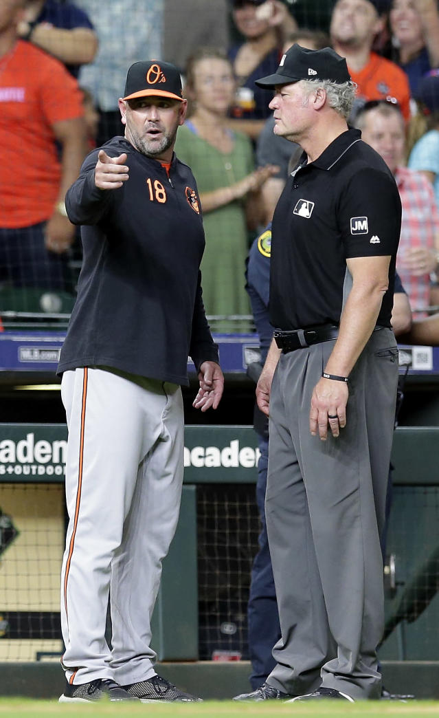 Baltimore Orioles manager Brandon Hyde (18) protests to third base umpire Ted Barrett after a video replay review ruled Houston Astros' Yuli Gurriel was safe at the plate after Orioles catcher Chance Sisco bobbled the ball on the play, allowing the Astros to win 4-3 in 11 innings in a baseball game Friday, June 7, 2019, in Houston. (AP Photo/Michael Wyke)