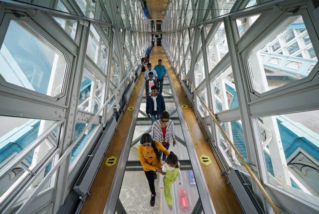 Visitors take in the view through the Glass Floor on the high-level walkway at Tower Bridge in London (Yui Mok/PA)