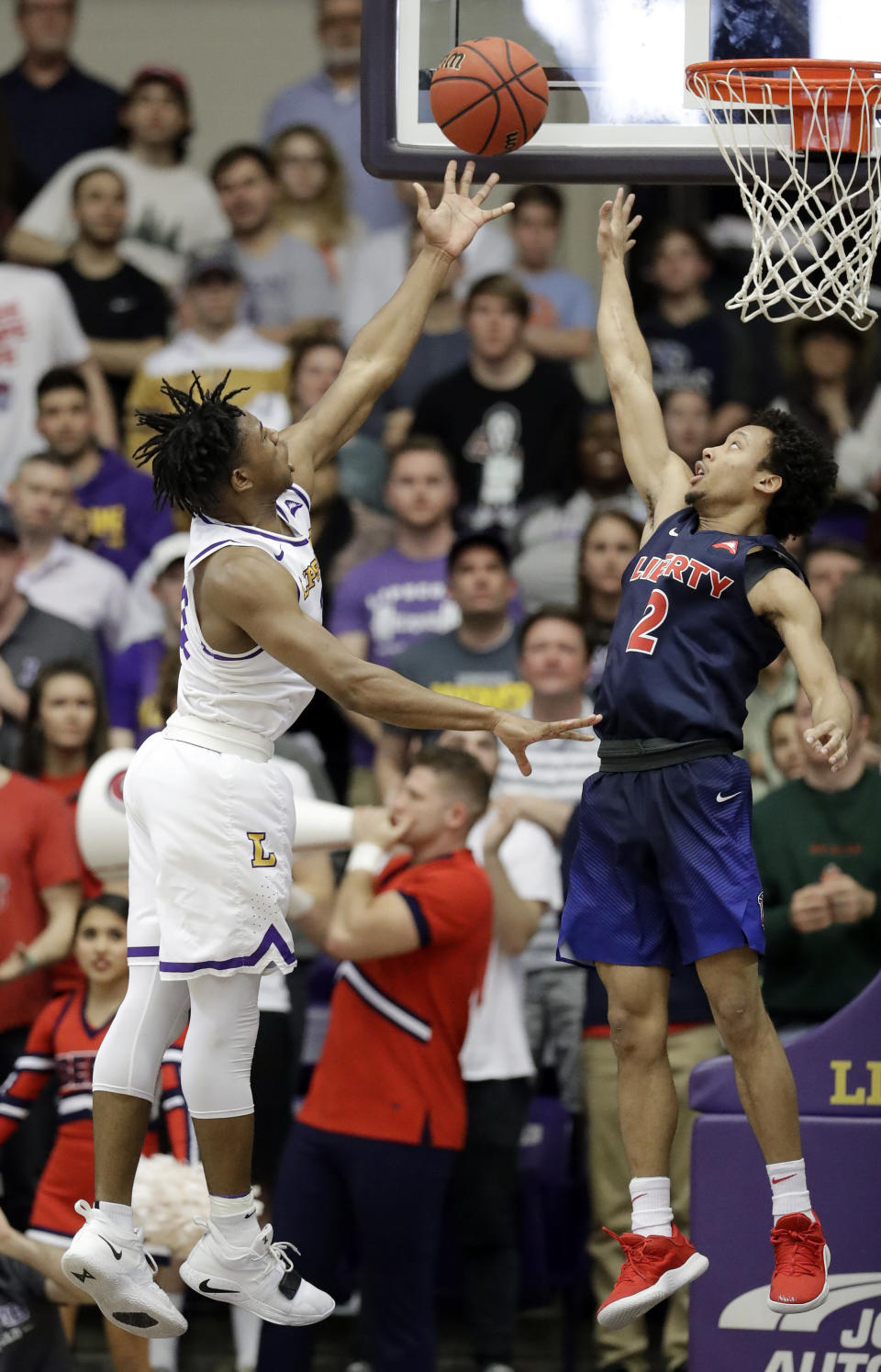 Lipscomb guard Kenny Cooper, left, shoots against Liberty guard Darius McGhee (2) in the first half of the Atlantic Sun NCAA college basketball tournament championship game Sunday, March 10, 2019, in Nashville, Tenn. (AP Photo/Mark Humphrey)