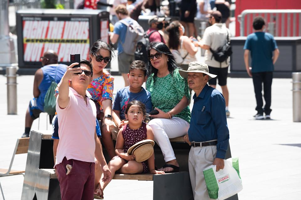 People take a selfie in Times Square on May 23, 2021 in New York City. On May 19, all pandemic restrictions, including mask mandates, social distancing guidelines, venue capacities and restaurant curfews were lifted by New York Governor Andrew Cuomo. (Noam Galai/Getty Images)
