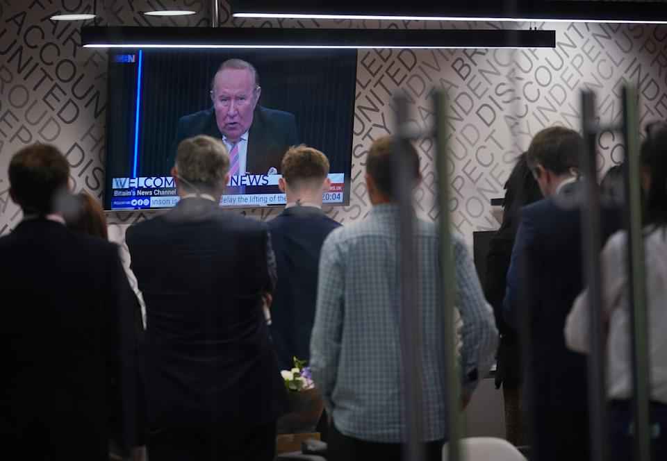 Staff in the green room watching a television screen showing presenter Andrew Neil broadcast from a studio, during the launch event for new TV channel GB News at The Point in Paddington, London. Picture date: Sunday June 13, 2021.